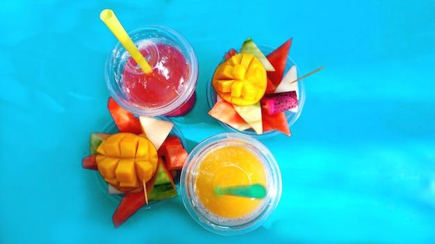 Frutas cítricas e fatias de frutas exóticas em um fundo azul - verão