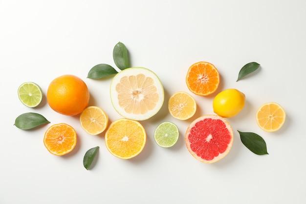 Frutas cítricas e folhas no fundo branco, vista superior
