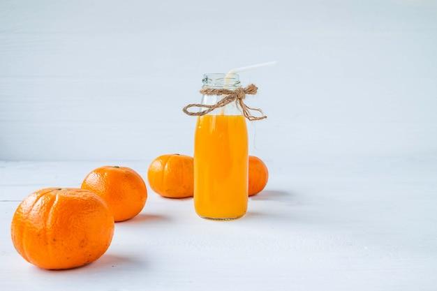 Frutas cítricas e garrafas de suco de laranja espremidas