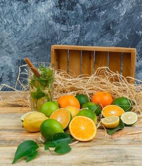 Frutas cítricas em close-up com caixa de madeira e bebida fermentada na placa de madeira