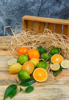 Frutas cítricas em close-up com caixa de madeira na placa de madeira