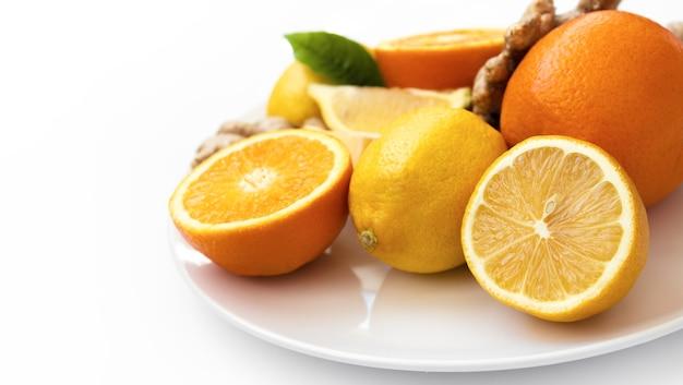 Frutas cítricas em um prato branco laranjas limões e gengibre em um prato branco em um