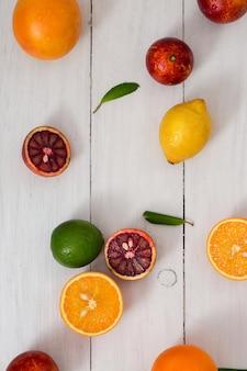 Frutas cítricas em uma mesa de madeira branca