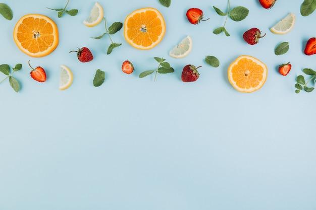 Frutas cítricas, folhas e morangos na mesa de madeira azul.