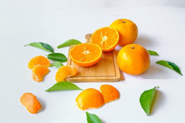 Frutas cítricas frescas com laranjas cortadas e folhas de laranja.