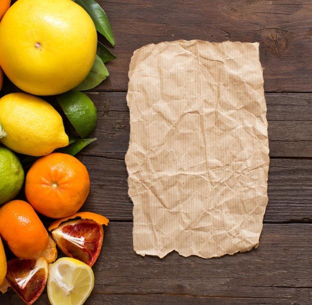 Frutas cítricas frescas com papel artesanal em madeira