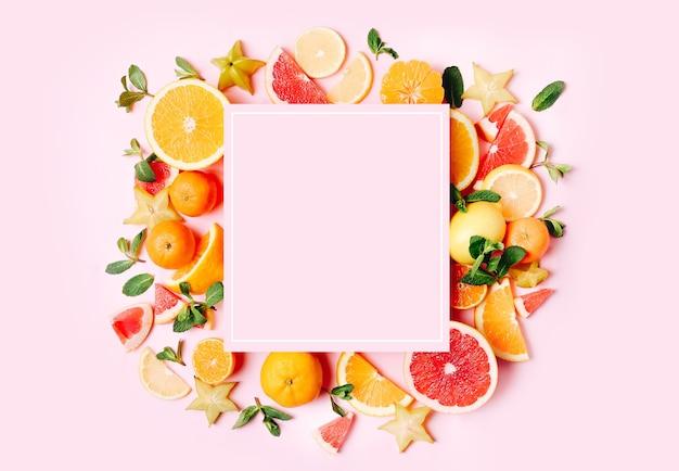 Frutas cítricas frescas formaram moldura em rosa.