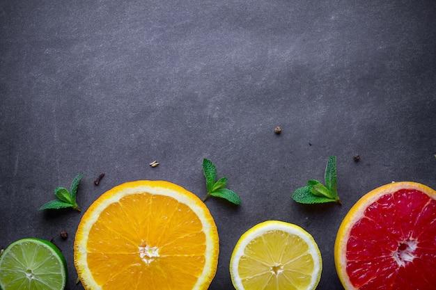Frutas cítricas frescas, maduras e folhas de hortelã verde sobre fundo escuro. alimentação e dieta saudáveis. copie o espaço