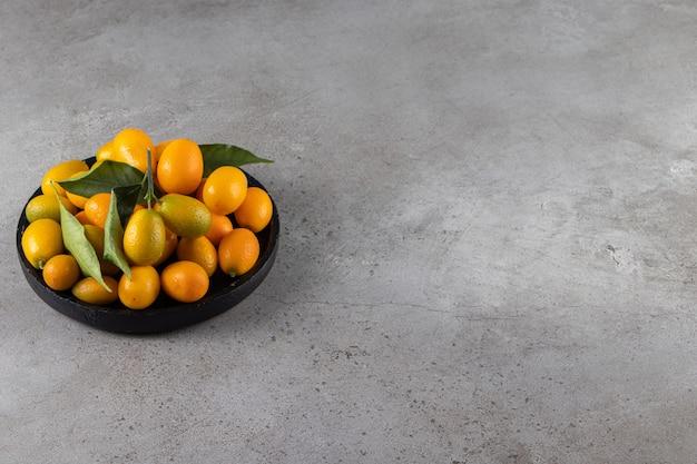Frutas cítricas inteiras e frescas de cumquat com folhas colocadas em uma tigela.