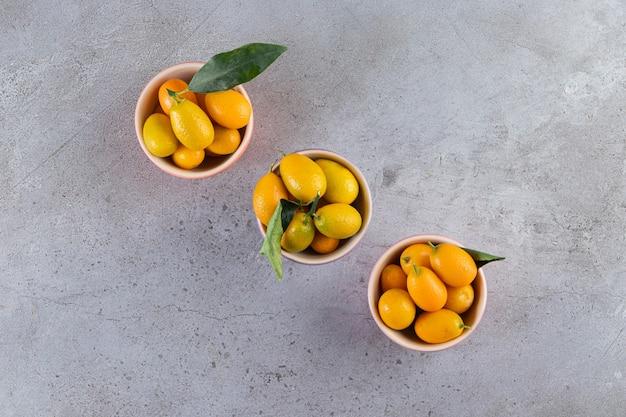 Frutas cítricas inteiras frescas cumquat com folhas colocadas em uma tigela.