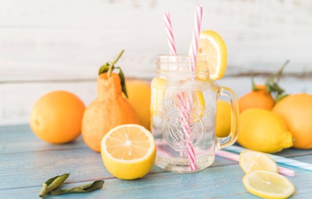 Frutas cítricas maduras e canudos em frasco