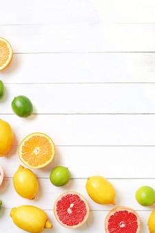 Frutas cítricas na mesa de madeira, vista superior, fundo copyspace