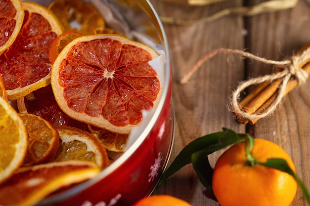 Frutas cítricas secas e tangerina fresca na mesa de madeira