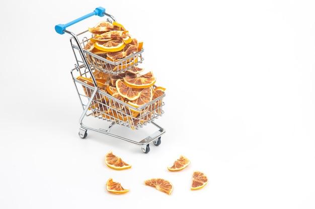 Frutas cítricas secas em um carrinho de compras em um fundo branco