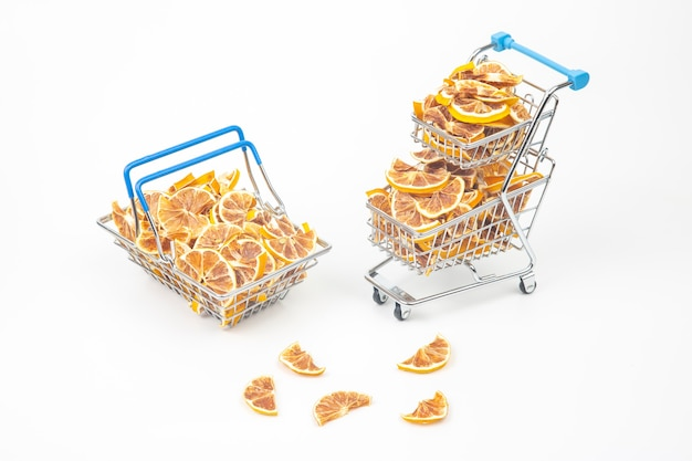 Frutas cítricas secas em uma cesta de mercado em um fundo branco.