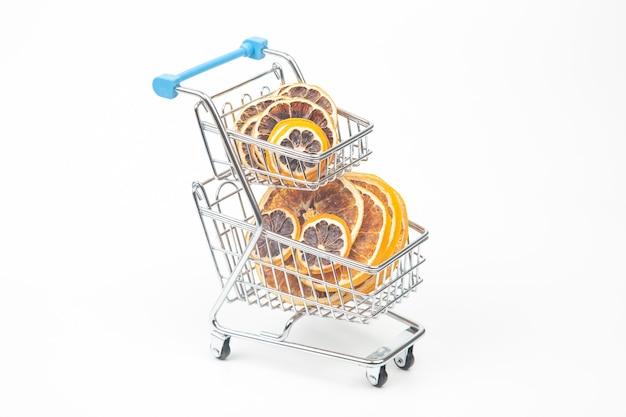 Frutas cítricas secas em uma cesta de mercado em uma superfície branca. alimentos vitamínicos