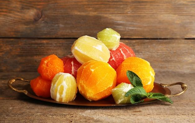 Frutas cítricas sem casca na bandeja, sobre fundo de madeira