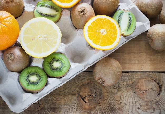 Frutas cítricas suculentas frescas em uma bandeja de caixa na superfície de madeira