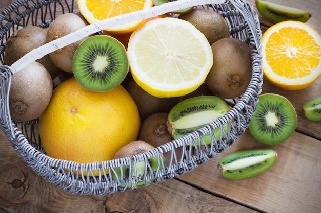 Frutas cítricas suculentas frescas em uma cesta na superfície de madeira