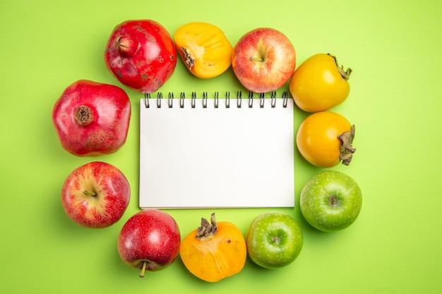 Frutas coloridas caquis maçãs romã ao lado do caderno branco