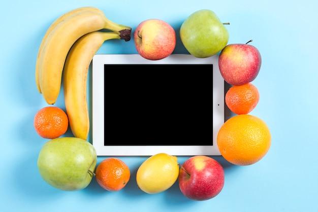 Frutas coloridas rodeadas com tablet digital sobre fundo azul