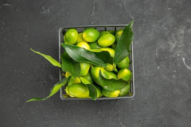 Frutas com folhas na cesta escura
