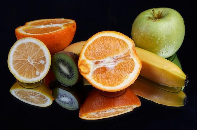 Frutas com respingos de água em fundo preto
