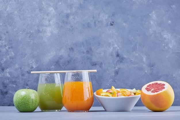 Frutas com salada e copos de suco.