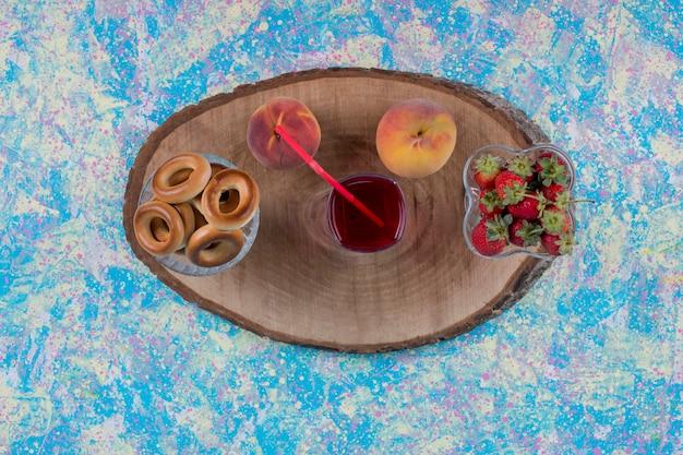Frutas com um copo de suco e biscoitos em uma travessa de madeira, vista superior