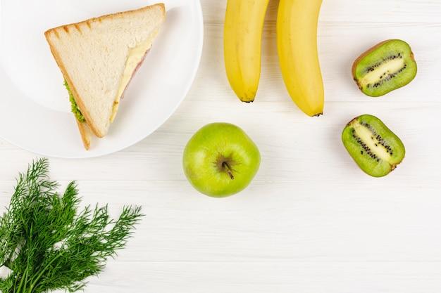 Frutas com um prato com sanduíche em uma mesa branca
