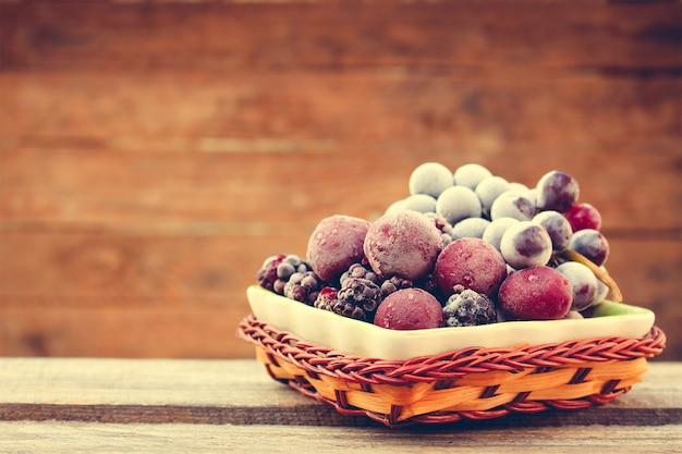 Frutas congeladas na madeira. imagem enfraquecida.