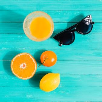 Frutas, copo de suco e óculos de sol na mesa