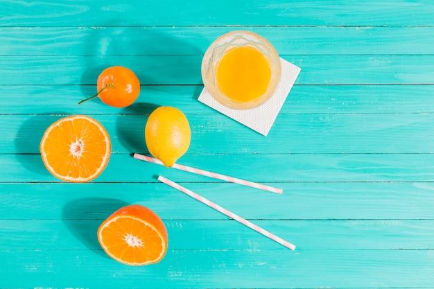 Frutas, copo de suco e palhas na mesa