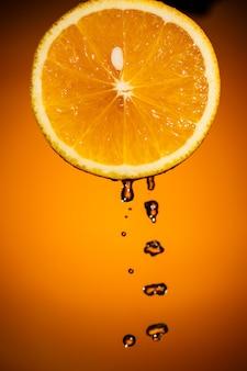 Frutas cortadas em fatias de laranja isoladas em fundo preto colorido