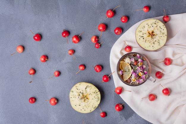 Frutas cortadas pela metade, cerejas e copo de suco com rodela de limão e flores em azul com toalha de mesa