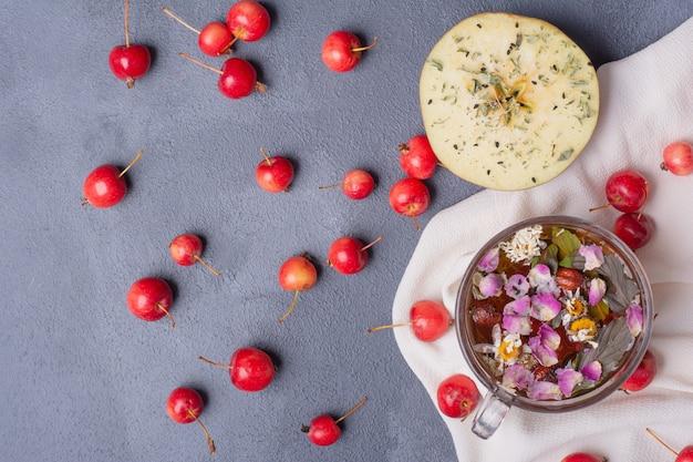 Frutas cortadas pela metade, cerejas e copo de suco com rodela de limão e flores em azul com toalha de mesa Foto gratuita