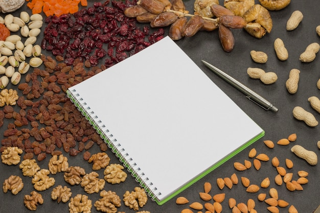 Frutas cristalizadas, frutas secas noz, caderno, caneta. lanche nutritivo para perda de peso e aumento da imunidade. adequação de alimentos saudáveis. . postura plana