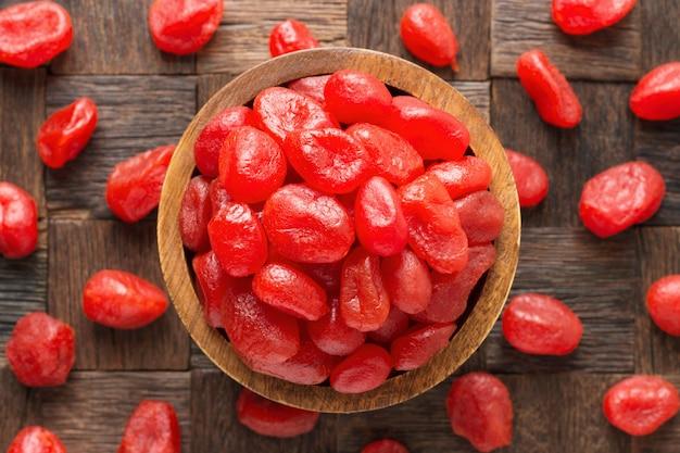Frutas cristalizadas, kumquat de toranja com açúcar na tigela de madeira, vista superior.
