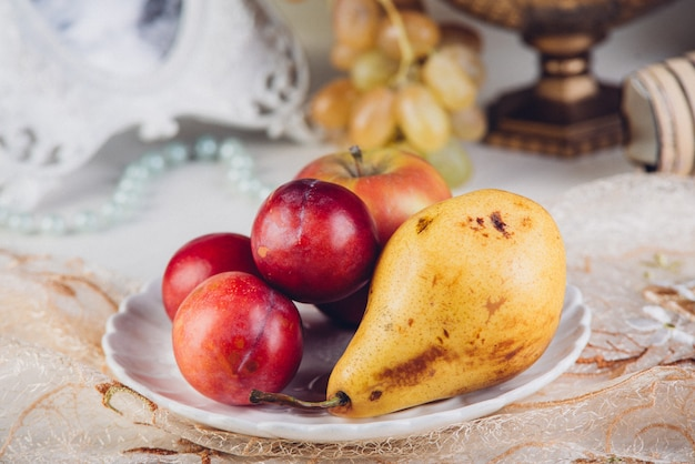 Frutas da estação, peras e ameixas em prato rústico.