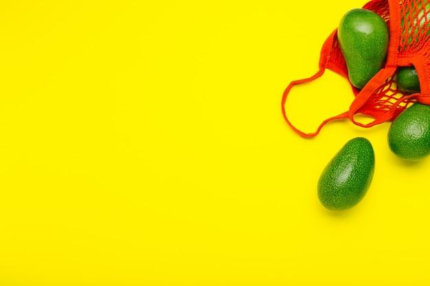 Frutas de abacate em saco ecológico de malha reutilizável vermelha. abacates de estilo mínimo lay plana sobre fundo amarelo, com espaço de cópia