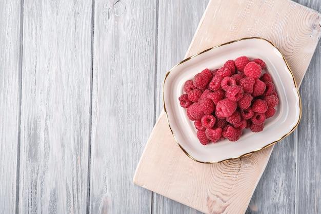 Frutas de framboesa em prato na velha tábua, pilha saudável de frutas de verão na mesa de madeira cinza, vista superior
