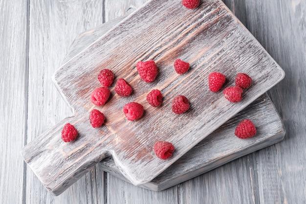 Frutas de framboesa em uma velha tábua de cortar, pilha saudável de frutas de verão em madeira cinza