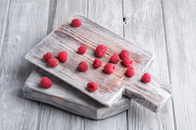 Frutas de framboesa na velha tábua de cortar, pilha saudável de frutas de verão na superfície de madeira cinza, vista de ângulo