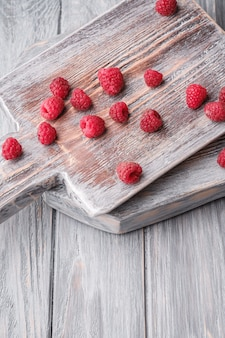 Frutas de framboesa na velha tábua de corte, pilha saudável de frutas de verão na tábua de madeira cinza, vista de ângulo