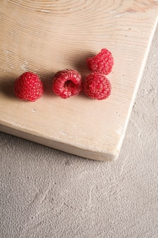 Frutas de framboesa na velha tábua de madeira, pilha saudável de frutas de verão na superfície de concreto de pedra, vista angular