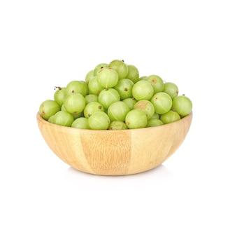 Frutas de groselha indiana em uma tigela de madeira em branco