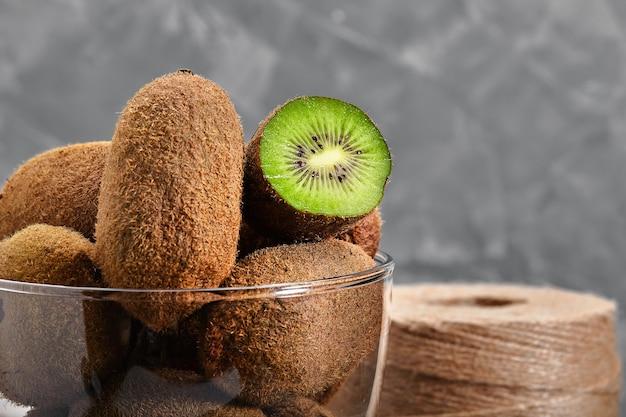 Frutas de kiwi cortadas pela metade em uma tigela de vidro em fundo liso temperamental preto escuro, vista de ângulo.