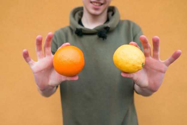 Frutas de laranja e limão nas mãos de um jovem. frutos de perto e em foco nas mãos de um jovem