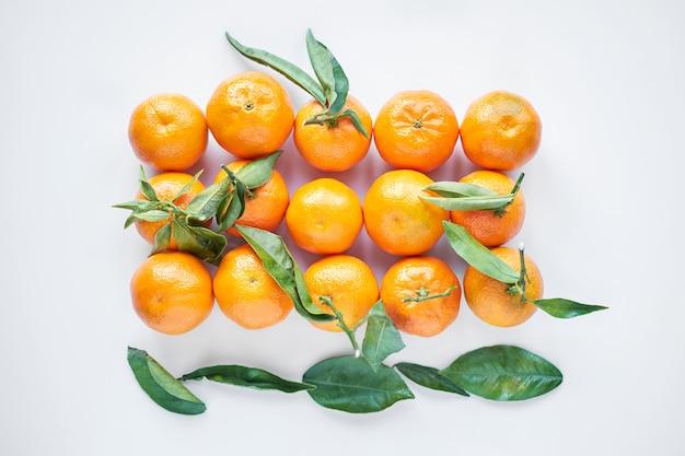 Frutas de natal. as tangerinas ou os mandarino frescos alaranjados com folhas verdes em um saco de papel encontram-se em um fundo branco.
