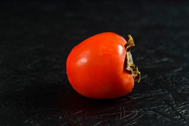 Frutas de outono. caqui em uma superfície de madeira preta